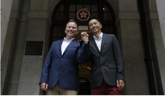 Angus Leung, with husband Scott Adams, won his legal battle last year. Photo: AP