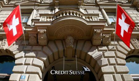 Switzerland's national flags fly beside the logo of Swiss bank Credit Suisse in Zurich