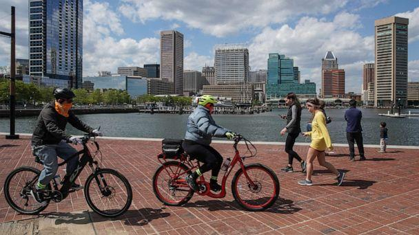 PHOTO: Baltimore residents walk and bike along the Inner Harbor promenade on May 12, 2020 in Baltimore. (Jemal Countess/Redux)