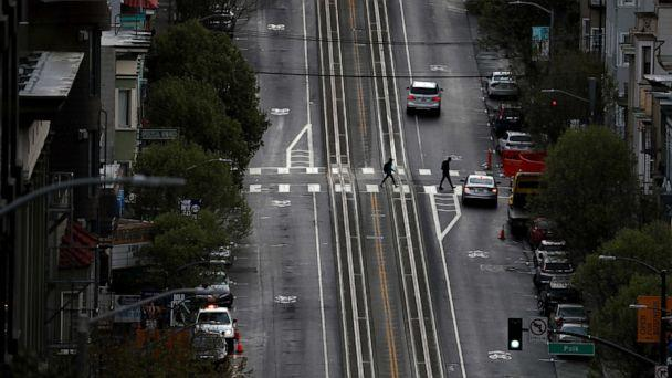 PHOTO: Two pedestrians cross an empty street, on March 16, 2020 in San Francisco. (Justin Sullivan/Getty Images)