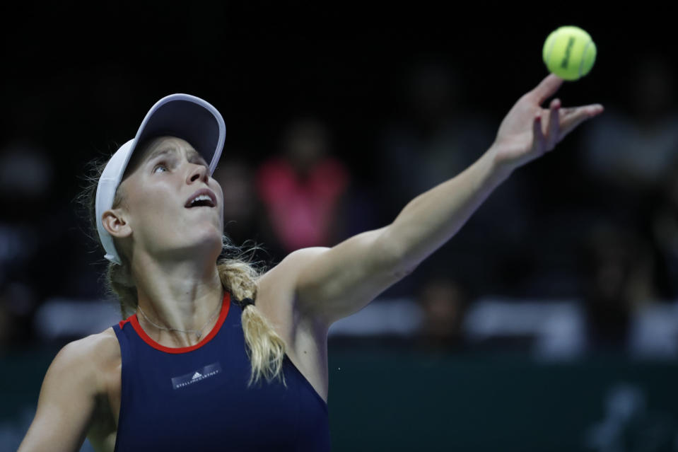 Caroline Wozniacki of Denmark serves while competing against Elina Svitolina of the Ukraine during their women's singles match at the WTA tennis finals in Singapore, Thursday, Oct. 25, 2018. (AP Photo/Vincent Thian)