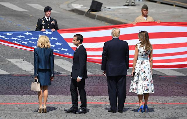 <p>(From right) First Lady Melania Trump, President Donald Trump, French President Emmanuel Macron and his wife Brigitte Macron, stand in front of the U.S. national flag held by soldiers, at the end of the annual Bastille Day military parade on the Champs-Elysees avenue in Paris on July 14, 2017. (Photo: Alain Jocard/AFP/Getty Images) </p>