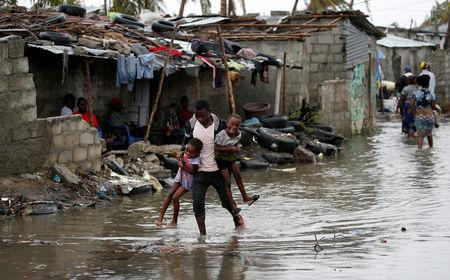 A man carries his children after Cyclone Idai at Praia Nova, in Beira, Mozambique, March 23, 2019. REUTERS/Siphiwe Sibeko