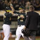 Oakland Athletics' Josh Reddick, center, is congratulated after hitting a grand slam off Boston Red Sox's Mark Melancon in the seventh inning of a baseball game Friday, Aug. 31, 2012, in Oakland, Calif. (AP Photo/Ben Margot)