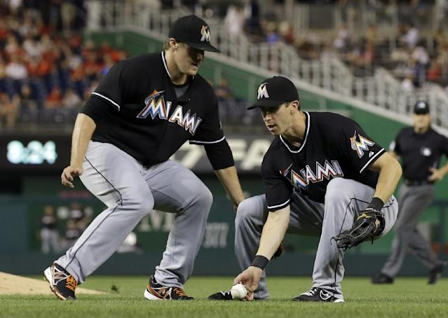 Miami Marlins starting pitcher Tom Koehler, left, watches as first baseman Ed Lucas grabs a bunt by Washington Nationals' Gio Gonzalez during the fifth inning of a baseball game at Nationals Park, Thursday, Aug. 29, 2013, in Washington. (AP Photo/Alex Brandon)