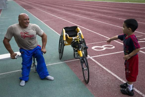 Jesus Aguilar, 48, a member of Venezuela's Paralympics team, shows his racing wheelchair to a child after a practice session in Caracas April 14, 2012.