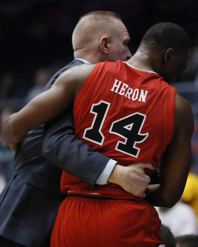 St. John's Mustapha Heron (14) hugs coach Chris Mullin, left, after fouling out during the second half against Arizona State in a First Four game of the NCAA men's college basketball tournament Wednesday, March 20, 2019, in Dayton, Ohio. (AP Photo/John Minchillo)