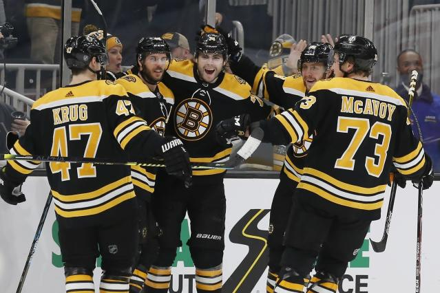 Boston Bruins' David Krejci, second from left, celebrates his 200th career goal with teammates during the third period of an NHL hockey game against the Carolina Hurricanes in Boston, Tuesday, Dec. 3, 2019. (AP Photo/Michael Dwyer)