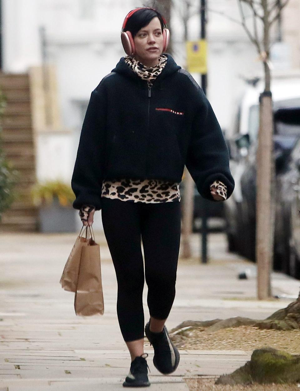 <p>Lily Allen totes some goodies while listening to tunes in London on Monday morning. </p>