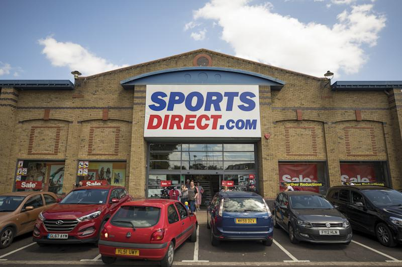 An automobile reverses from a parking space outside a Sports Direct International Plc store. Photo: Jason Alden/Bloomberg