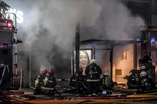 A photo released by Agencia Telam shows firefighters after two explosions at a perfume store killed two of their colleagues and injured 15 others, in Buenos Aires on June 2, 2020