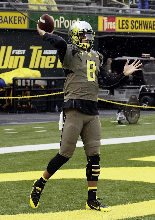 Oregon quarterback Marcus Mariota wears a knee brace on his left leg as he warms up before an NCAA college football game against Utah in Eugene, Ore., Saturday, Nov. 16, 2013. (AP Photo/Don Ryan)