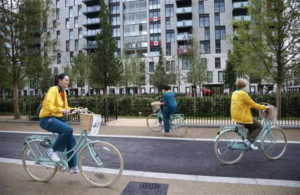 Kylie Peake (L), an official from Australia, rides a bicycle with a colleague at the athletes village at the Olympic Park, in London July 20, 2012.