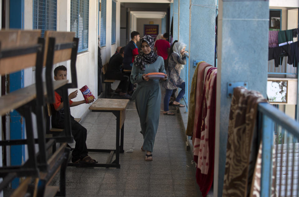 Palestinians take shelter at a school run by the U.N. after fleeing heavy Israeli missile strikes in the outskirts of Gaza City, Wednesday, May 19, 2021. The Gaza Strip's already feeble health system is being brought to its knees by the fourth war in just over a decade. At the school, no one wore a mask or could do any social distancing in the cramped quarters. (AP Photo/Khalil Hamra)