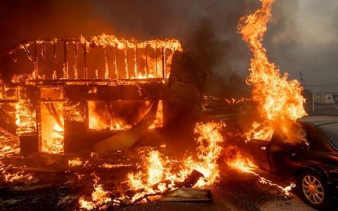 Flames consume a car and building as the Camp Fire tears through Paradise, California - Credit:  Noah Berger/AP