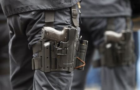 A Heckler & Koch P30 handgun is seen strapped to the leg of a German police officer in Munich in this February 2, 2013 file photo. REUTERS/Michaela Rehle/Files