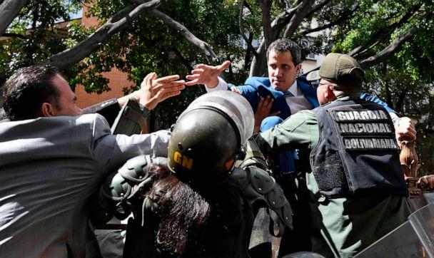 PHOTO: Venezuelan opposition leader Juan Guaido is blocked by security forces as he tries to reach the National Assembly building in Caracas by climbing over a fence, on Jan. 5, 2020. (Federico Parra/AFP via Getty Images)