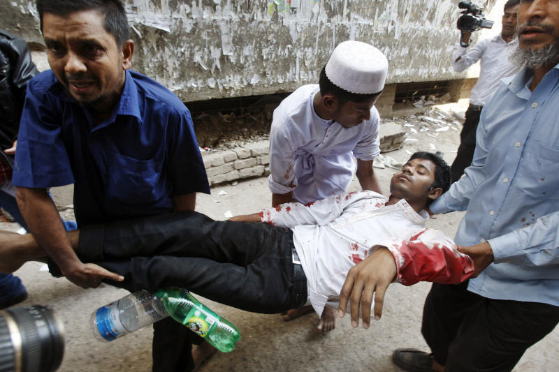 Bangladeshi people carry an injured Muslim activist during a protest in Dhaka, Bangladesh, Friday, Feb. 22, 2013. Police fired rubber bullets and tear gas Friday to disperse thousands of rampaging protesters from Islamic parties, leaving two people killed and dozens injured, police and witnesses said. The nationwide protests were held separately by Jamaat-e-Islami, the country's largest Islamic party and an alliance of 12 other smaller Islamic groups to denounce the war crimes trial of its top leaders. (AP Photo/Pavel Rahman)