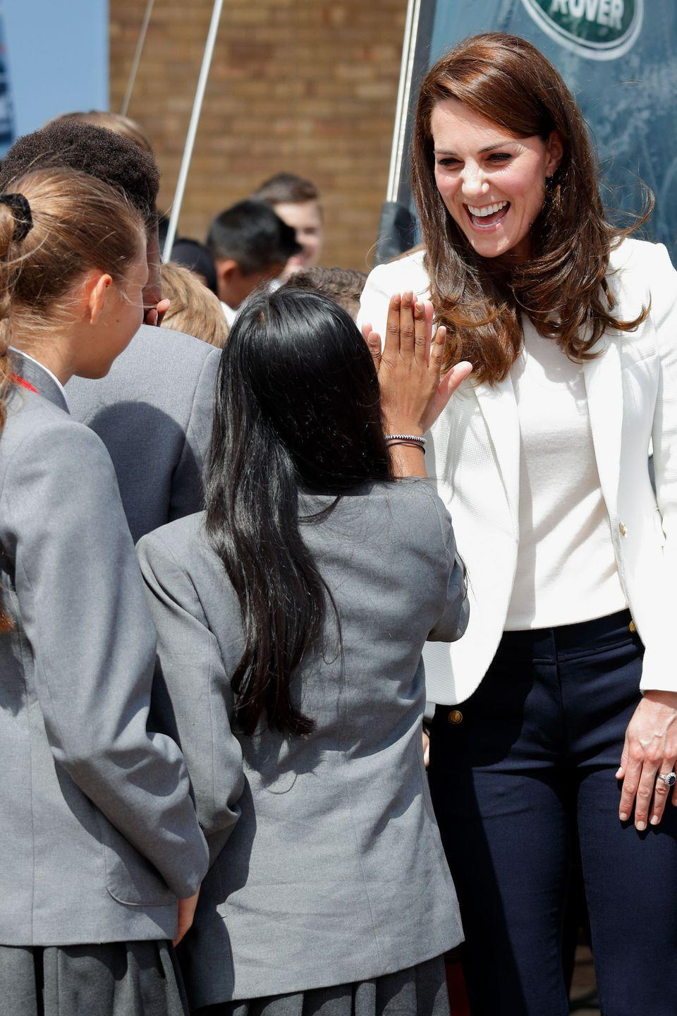 <p>Kate shares a high-five with school girls as she arrives at the 1851 Trust roadshow at the Docklands Sailing and Watersports Centre.</p>