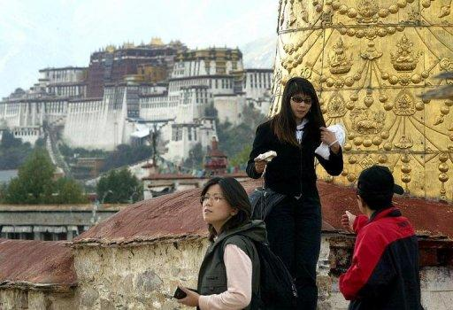 This file photo shows Chinese tourists visiting Jokhang Temple in Lhasa, with a view of the Potala Palace in the background. China's propaganda chief has ordered officials to intensify the fight against separatism in Tibet, a report said, following a series of self-immolations in protest at Beijing's rule