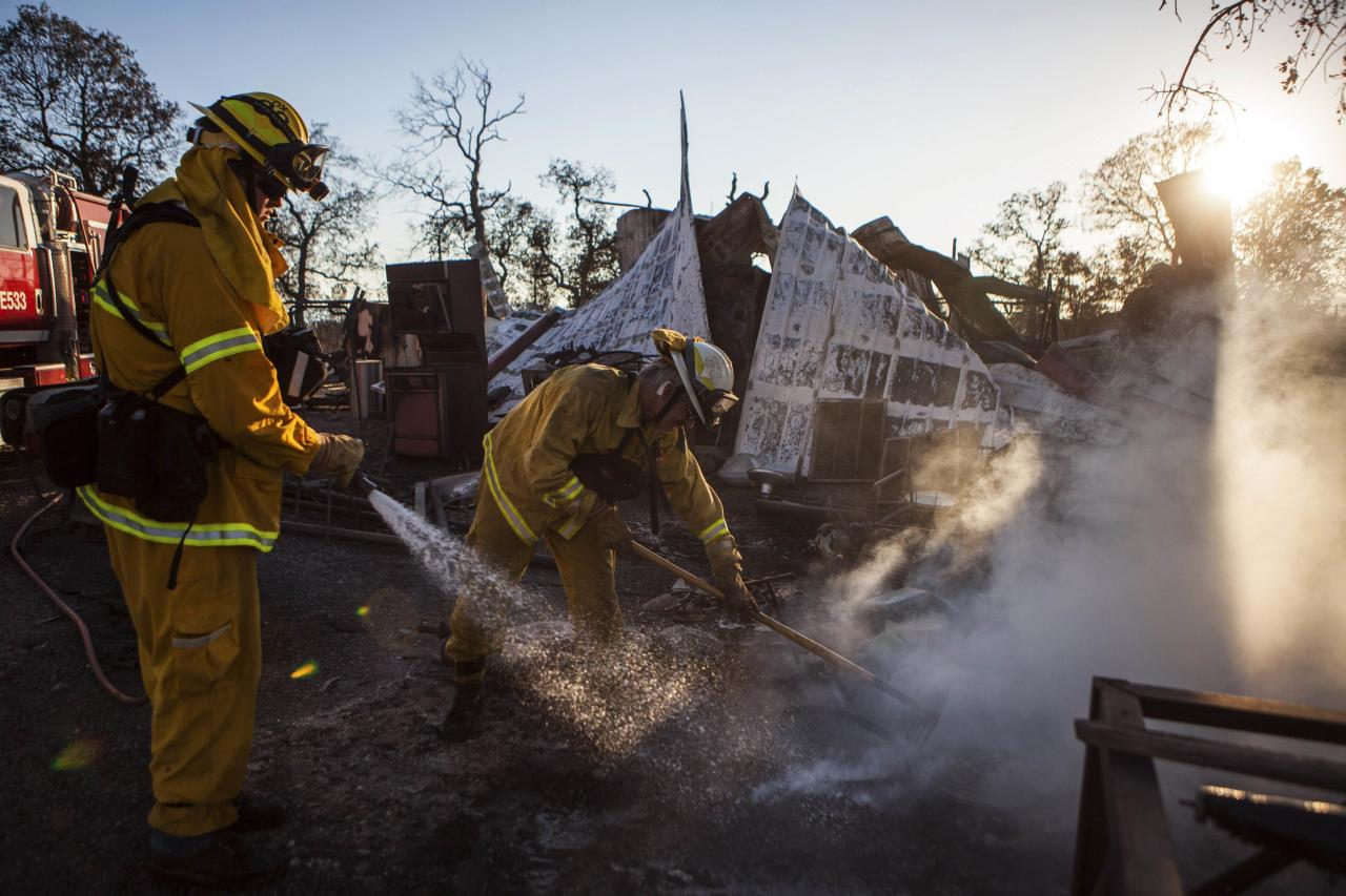 Shasta County firefighters Zach Lacy (L) and Bob Baker spray water on a home burnt by the Clover Fire in Happy Valley, California September 10, 2013. The fast-moving wildfire ripped through rolling hills and ranch land in rural northern California on Tuesday, after destroying 30 homes overnight and prompting more than 500 area residents to evacuate, fire officials said. REUTERS/Max Whittaker (UNITED STATES - Tags: ENVIRONMENT DISASTER TPX IMAGES OF THE DAY)