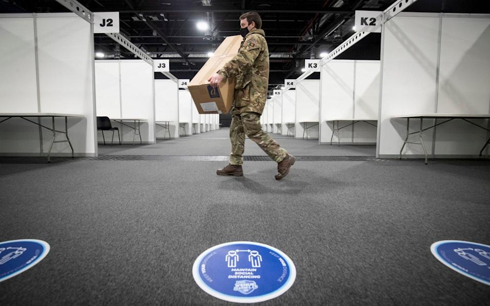 A member of the Royal Scots Dragoon Guard carries in supplies at the P&J Live mass vaccination centre in Aberdeen - PA