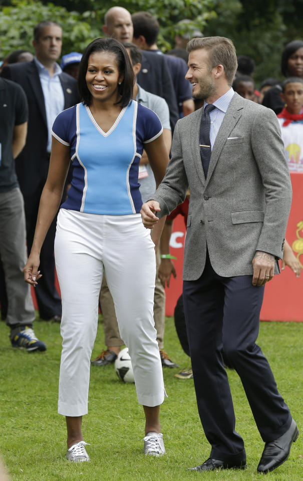 U.S. first lady Michelle Obama, left, walks with soccer player David Beckham during a 'Let's Move!' event for about 1,000 American military children and American and British students at the U.S. ambassador's residence in London, ahead of the 2012 Summer Olympics, Friday, July 27, 2012. (AP Photo/Lefteris Pitarakis)