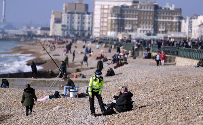 A community support officer speaks to people enjoying the sunshine on Brighton beach in Sussex. Picture date: Sunday February 28, 2021.