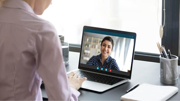 Indian girl communicate with friend on-line by video call, pc screen view over female shoulder. Mental health expert online therapy, colleagues work on common project use videoconferencing app concept