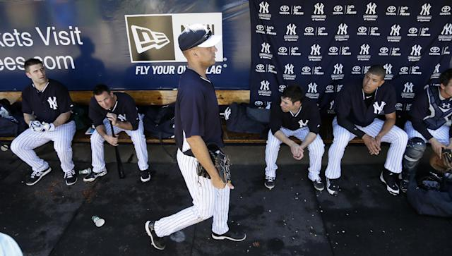 New York Yankees shortstop Derek Jeter, center, walks through the dugout during spring training baseball practice Thursday, Feb. 20, 2014, in Tampa, Fla. (AP Photo/Charlie Neibergall)