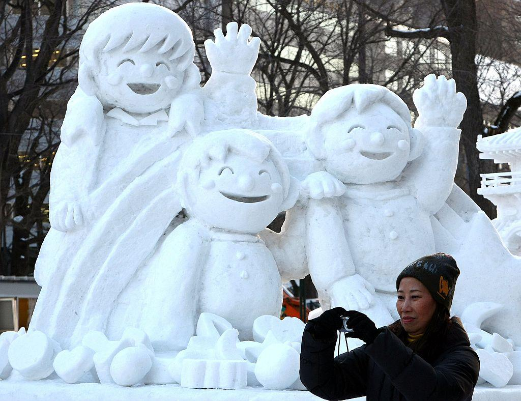 A woman takes photos of ice sculptures ahead of the 60th Sapporo Snow Festival at Odori Park in 2009 in Sapporo, Japan.