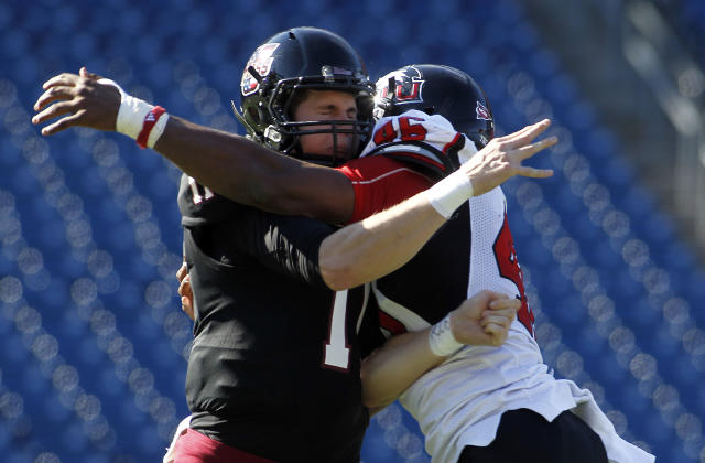 Massachusetts quarterback Mike Wegzyn (11) is pressured by Northern Illinois defensive end George Rainey (46) during the first half of an NCAA football game in Foxborough, Mass., Saturday, Nov. 2, 2013. (AP Photo/Stew Milne)