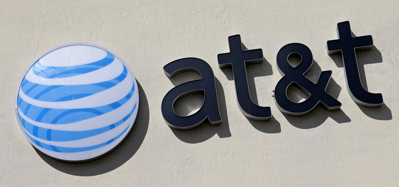 FILE - This Wednesday, Feb. 8, 2017, file photo shows the AT&T sign at a store in Hialeah, Fla. The Justice Department has opened an antitrust investigation into whether AT&T, Verizon and a standards-setting group worked together to stop consumers from easily switching wireless carriers. The companies confirmed the inquiry in separate statements late Friday, April 20, 2018, in response to a report in The New York Times. (AP Photo/Alan Diaz, File)