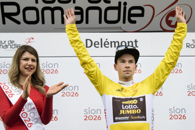 The overall leader Primoz Roglic from Slovenia of team Lotto NL-Jumbo celebrates on the podium with the yellow jersey after the first stage, a 166,6 km race between Fribourg and Delemont during the 72th Tour de Romandie UCI ProTour cycling race in Delemont, Switzerland, Wednesday, April 25, 2018. (Jean-Christophe Bott/Keystone via AP)