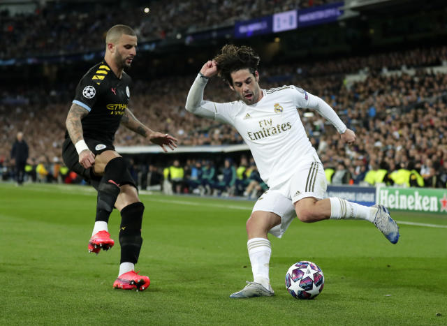 """FILE - In this Wednesday, Feb. 26, 2020 file photo, Real Madrid's Isco, right, duels for the ball with Manchester City's Kyle Walker during the Champions League, round of 16, first leg soccer match between Real Madrid and Manchester City at the Santiago Bernabeu stadium in Madrid, Spain. Manchester City's appeal against a two-year ban from European soccer will be heard over three days in June. The Court of Arbitration for Sport says it has set aside June 8-10 for the case. It is unclear if a hearing will be held in person at the court or by video link. No timetable was set for a verdict but a ruling is needed before English teams enter next season's Champions League draw. Man City was banned by UEFA in February for """"serious breaches"""" of financial monitoring rules and failing to cooperate with investigators. (AP Photo/Manu Fernandez, File)"""