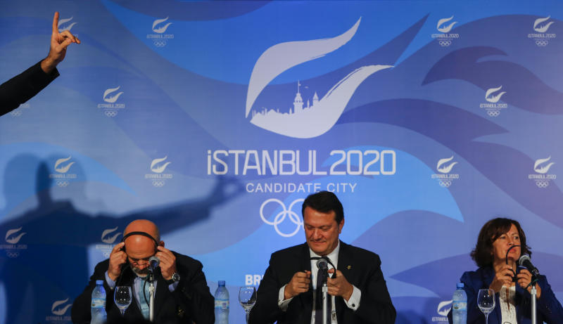 Istanbul 2020 Sports Director Alp Berker, from left to right, Istanbul 2020 Bid Chairman Hasan Arat and Secretary General of Turkish National Olympic Committee Nese Gundogan put on their headsets at a news conference in Buenos Aires, Argentina, Friday, Sept. 6, 2013. During the Sept. 4-10 International Olympic Committee (IOC) Executive Board meetings in Buenos Aires, members will elect the host city for the 2020 Summer Olympics Games, with candidates being Madrid, Istanbul and Tokyo, as well as choose a new IOC president and add a sport to the 2020 program. (AP Photo/Ivan Fernandez)