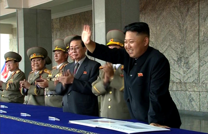 In this image taken from video North Korean leader Kim Jong Un, right, smiles as he waves to spectators and participants of a military parade celebrating the 65th anniversary of the country's founding, Monday, Sept. 9, 2013, in Pyongyang, North Korea. (AP Photo/KRT via AP Video) TV OUT, NORTH KOREA OUT