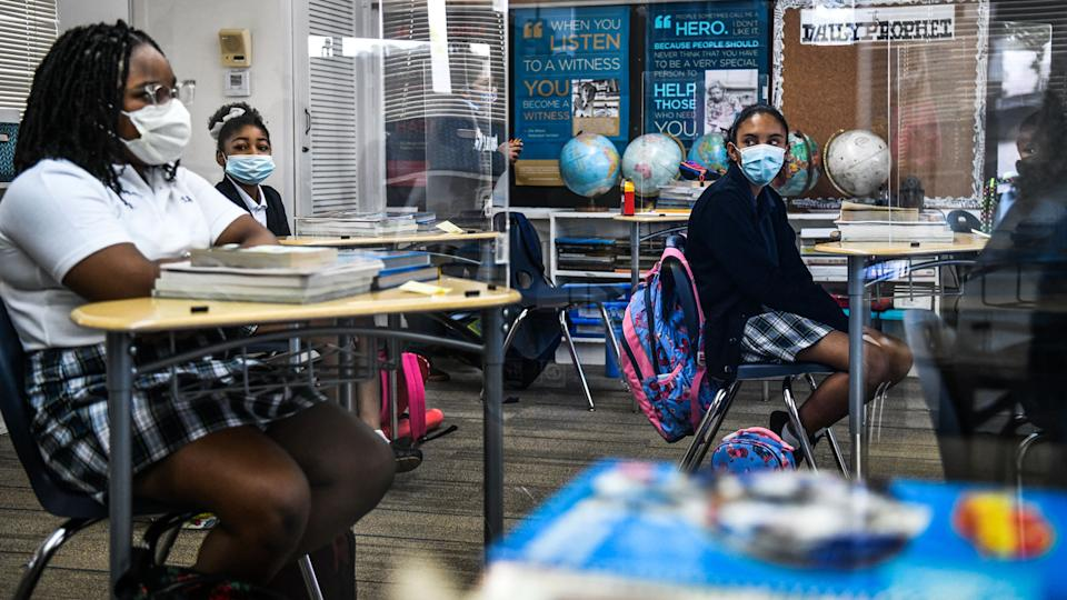Students in facemasks on their first day in school after summer vacation at the St. Lawrence Catholic School  in north of Miami on Wednesday.
