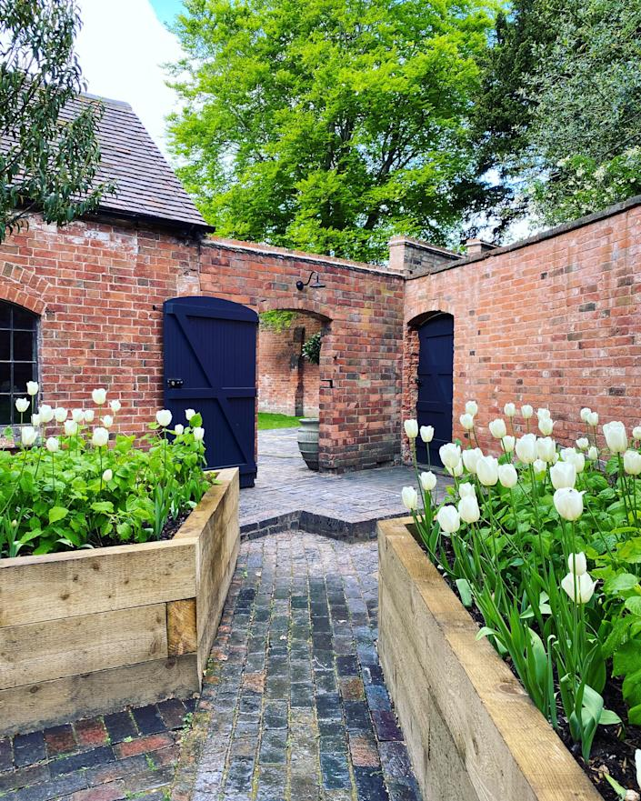 Raised planters with white tulips punctuate the cobbled courtyard of the service quarters.