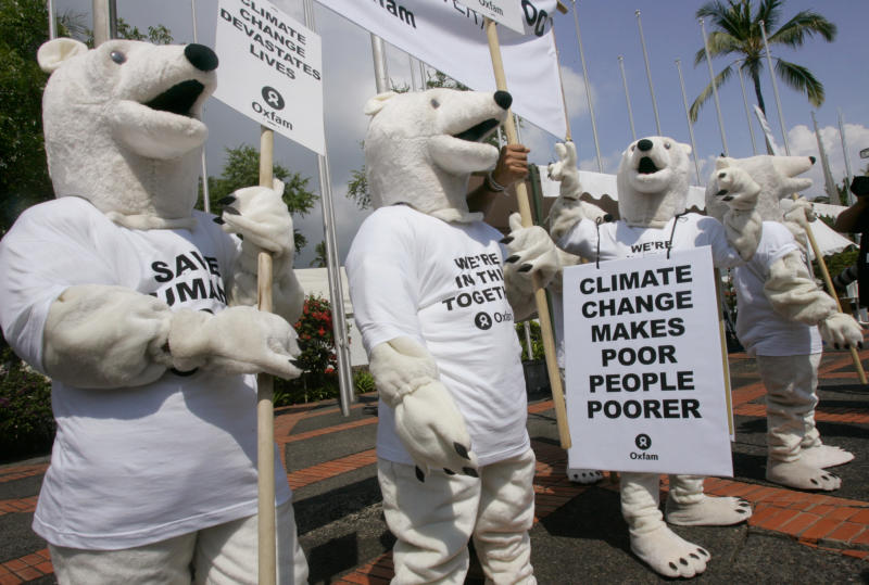 "FILE - In this Dec. 6, 2007, file photo, Oxfam activists wearing polar bear costumes stage a demonstration outside the venue of the U.N. climate change conference in Nusa Dua, Bali island, Indonesia. If you think of climate change as a hazard faced by some far-off polar bear decades from now, you're mistaken. That's the message from top climate scientists gathering in Japan this week to assess the impact of global warming. ""The polar bear is us,"" says Patricia Romero Lankao of the federally funded National Center for Atmospheric Research in Boulder, Colo. (AP Photo/Dita Alangkara, File)"