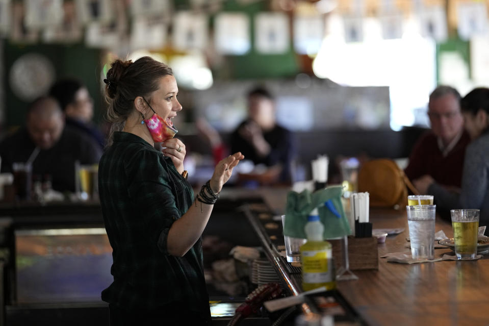 Bartender Alyssa Dooley talks with customers at Mo's Irish Pub, Tuesday, March 2, 2021, in Houston. Texas Gov. Greg Abbott announced that he is lifting business capacity limits and the state's mask mandate starting next week. (AP Photo/David J. Phillip)