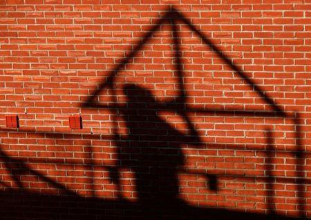FILE PHOTO: A construction worker casts a shadow as he works on a building site in Aylesbury