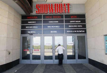 A man tries to peek into the closed Showboat Casino Hotel in Atlantic City, New Jersey September 1, 2014. REUTERS/Tom Mihalek