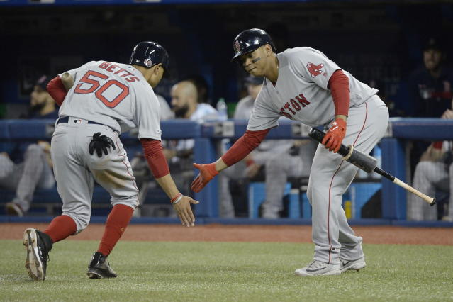 Boston Red Sox's Mookie Betts (50) celebrates with Rafael Devers (11) after Bett scored against the Toronto Blue Jays during the third inning of a baseball game Wednesday, May 22, 2019, in Toronto. (Nathan Denette/The Canadian Press via AP)