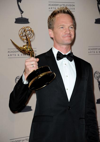 """Neil Patrick Harris poses backstage with his award for outstanding special class programs for the """"66th Annual Tony Awards"""" at the Primetime Creative Arts Emmy Awards at the Nokia Theatre L.A. Live on Sunday, Sept. 15, 2013, in Los Angeles. (Photo by Richard Shotwell/Invision/AP)"""