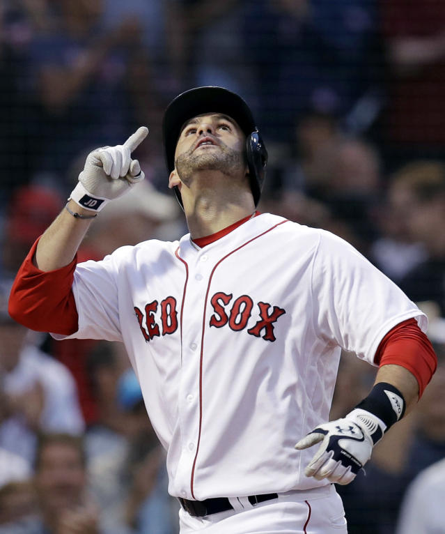 Boston Red Sox's J.D. Martinez points upward as he crosses home plate after belting a three-run home run off Los Angeles Angels starting pitcher Andrew Heaney during the second inning of a baseball game at Fenway Park in Boston, Wednesday, June 27, 2018. (AP Photo/Charles Krupa)