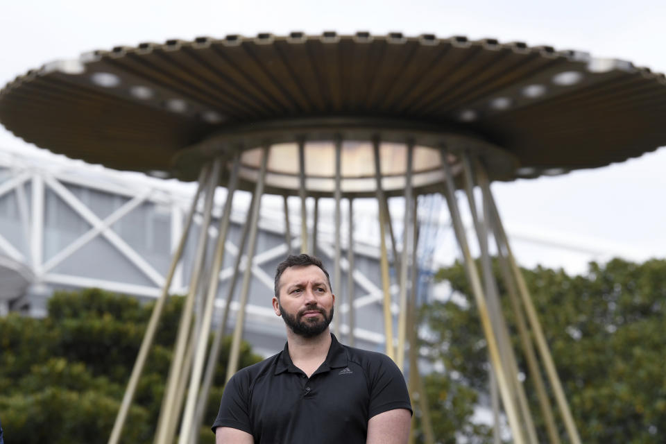 Australian Olympian Ian Thorpe stands in front of the Sydney 2000 Olympic Cauldron as it's lit to celebrate the 20th anniversary of the Sydney 2000 Olympic Games in Sydney, Tuesday, Sept. 15, 2020. With three swim gold medals and two silver, several in world-record time, Thorpe, then only 17, was the most successful Australian performer in Sydney. (Dean Lewins/AAP Image via AP)