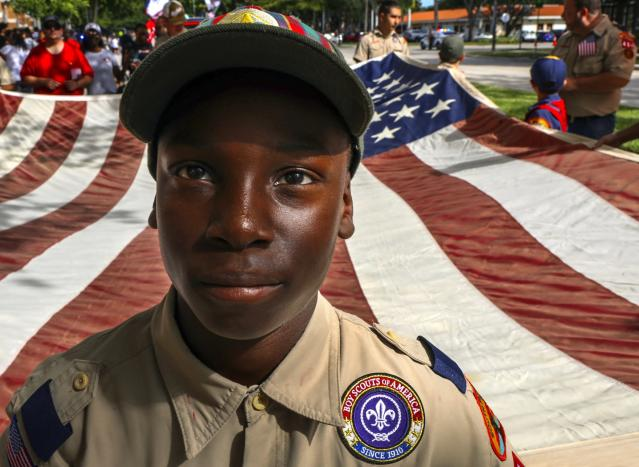 Boy Scout Christian Alize leads Cub and Boy Scouts of Troop 484 and 584 in carrying a large American flag as they participate in the city of Miami Lakes, Fla. on Nov. 10, 2019. (Photo: Carl Juste/Miami Herald via AP)