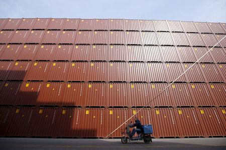 FILE PHOTO: A man rides a vehicle past container boxes at a port in Shanghai