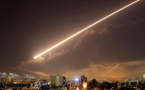 Damascus skies erupt with service to air missile fire as the U.S. launches an attack on Syria - Credit: AP